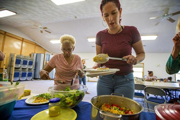 Genie Garda, right, and Amada Gregory grab food at the potluck in Dracut. Both women relocated from Puerto Rico after Maria. (Jesse Costa/WBUR)