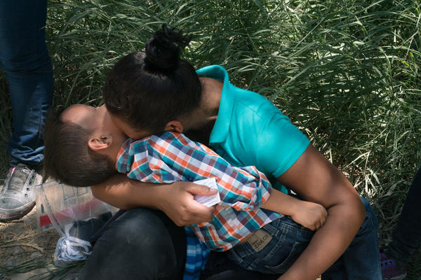 Cilian Xiomara Santos, 23, and her son, Erlin Joel Santos, 5, laugh for a moment after they turned themselves in to Customs and Border Protection, as they wait for a bus to pick them up. Many of the migrants feel relieved that they have finally made it to the U.S.