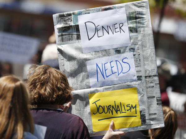 An <em>Denver Post</em> employee holds up a sign during a rally against the paper's ownership group, Alden Global Capital, on May 8 outside the paper's office. A series of layoffs have slashed the paper's newsroom staff.