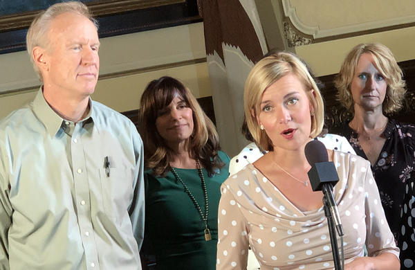 Rep. Sara Wijcicki, at microphone, sponsored legislation to make Springfield the default site for new or vacant state jobs. Gov. Bruce Rauner, left, signed the legislation Thursday, August 9, 2018.