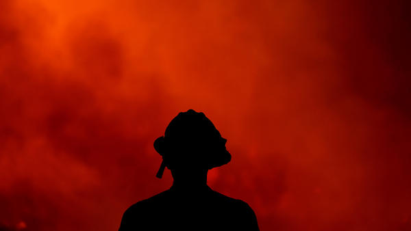 A firefighter keeps watch Thursday on the Holy Fire, which has ravaged the Cleveland National Forest in Lake Elsinore, Calif. Authorities say they believe Forrest Gordon Clark, 51, is the arsonist who set the forest ablaze.