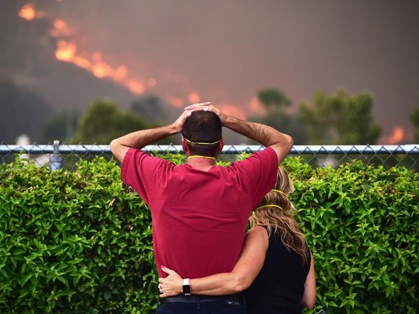 Ziggy Torok and Starla Affatati watch helplessly Thursday as the flames of the Holy Fire close in on Torok's home in the Rice Canyon neighborhood of Lake Elsinore, Calif.