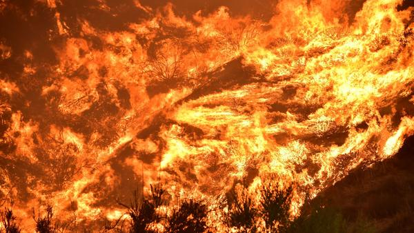 Flames engulf a hillside Thursday in Lake Elsinore, Calif. Firefighters say the blaze, which has burned through more than 10,000 acres and forced the evacuations of 20,000 people, is just 5 percent contained.