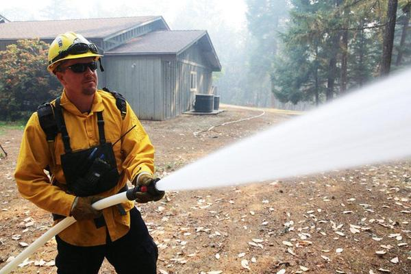 <p>Klamath County firefighter Jeff Frost runs a structure protection drill at a home on a secluded cul-de-sac near the Rogue River. Its owners evacuated as the Taylor Creek Fire burned closer.</p>