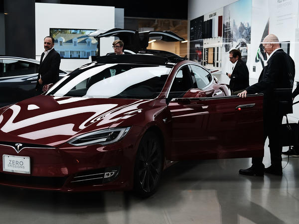People look at cars at a Tesla showroom in New York City. Tesla CEO Elon Musk, reportedly under scrutiny by federal regulators for earlier statements, says Saudi Arabia's sovereign wealth fund is looking to diversify away from oil with a bigger investment in the electric car company.