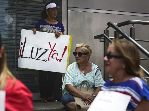 "In this May 2018 photo, residents without power from the municipality of Yabucoa protested outside the Electric Power Authority office. A protester's sign read ""Light now!"""