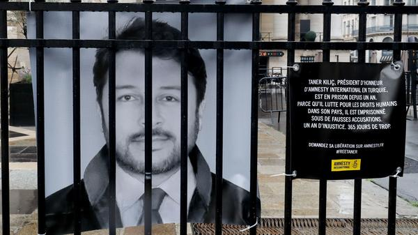 "A poster of Taner Kiliç hangs on the fence of the historic French stock market building ""Palais Brongniart"" in Paris in June. On Wednesday, the honorary chair of Amnesty International Turkey was freed after more than a year in prison."