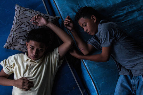 "Chino, left, and his friend Tito cool off at a gang house in San Pedro Sula. Chino joined a gang at 14 and has the privileges that come with being a member: respect, fear, power — but also ""a cell phone and chains,"" says Ayuso. Ayuso also heard Tito — who is not in a gang — say he hopes to be like Chino someday."