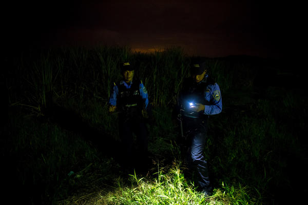 "Police stand before a site where bodies are dumped in San Pedro Sula, investigating the latest corpse. ""It was another body in a potato sack, contorted to fit in the bag,"" says Ayuso.<strong> </strong>"