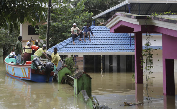 Volunteers in a boat help to rescue stranded people from a flooded area in Chengannur in the southern state of Kerala, India, on Sunday.