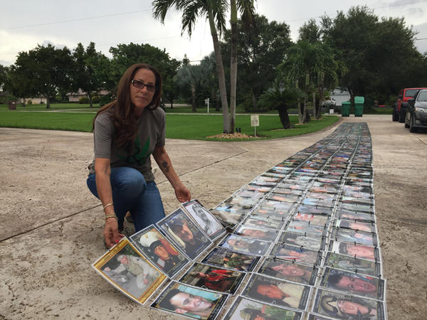Janine Lutz in front of her Memorial Wall, which she built with photos of veterans who committed suicide. Families of the vets send photos to her through her Live To Tell foundation.