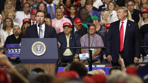 President Trump listens as Florida GOP gubernatorial candidate Ron DeSantis speaks at a Make America Great Again Rally in Tampa last month.