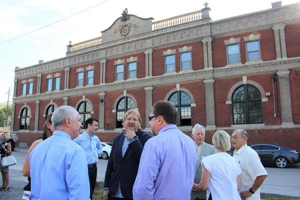 Ryan Maybee, front middle, and Andy Rieger, back left, announced Tuesday J. Rieger & Co. would expand operations into the historic Heim Brewery building.