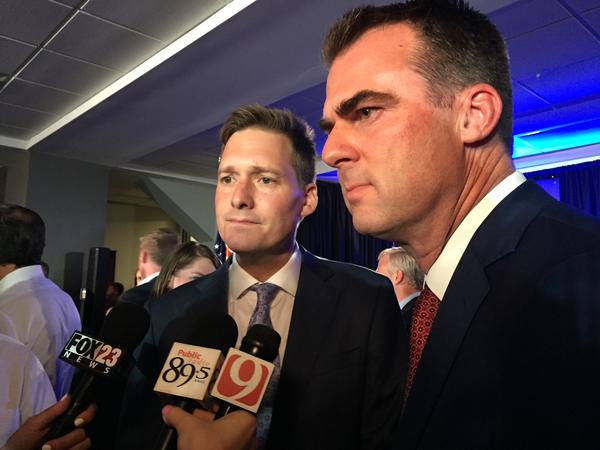 Matt Pinnell, left, and Kevin Stitt talk to reporters at a watch party in Tulsa on Aug. 28, 2018.