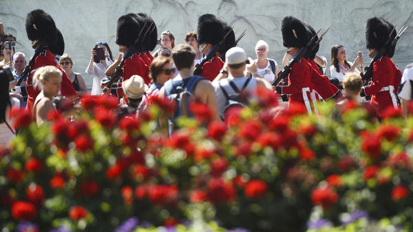Spectators gather daily to watch the changing of the guard at Buckingham Palace in London. On Friday, a military band paid tribute to Aretha Franklin at the ceremony.
