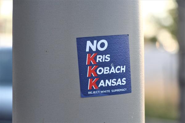 A sticker on a traffic pole in Lenexa this month attempts to link GOP gubernatorial candidate Kris Kobach to white supremacy.