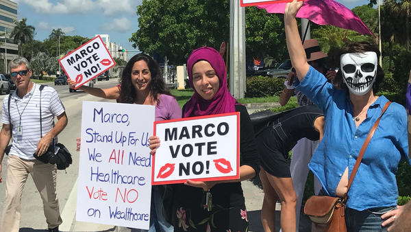 """Protesters march outside U.S. Sen. Marco Rubio's office demanding he vote """"no"""" on the Senate health care bill near the intersection of NW 36th St. and NW 87th Ave. in Doral."""