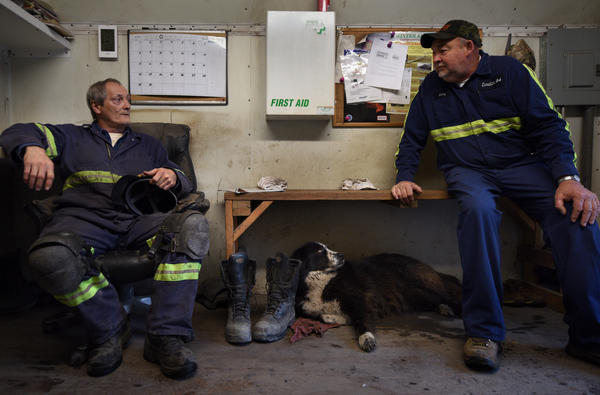 "Dotson (right) and his employee Bill Spencer talk as local dog Sweetie hangs out. Spencer says if the mine goes out of business, he's ""done for."""