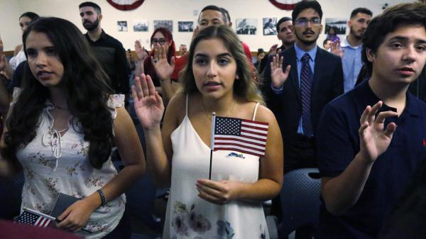 Ericka Ames, center, of Nicaragua recites the Oath of Allegiance during a naturalization ceremony at the U.S. Citizenship and Immigration Services in Miami. The backlog of citizenship applications has increased dramatically under the Trump administration.
