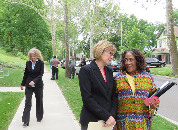 Jackson County Prosecutor Jean Peters Baker, center, is taking over violence prevention group COMBAT. Last May, Baker delivered a warning letter to a home riddled with gunfire, accompanied by Manheim neighborhood president Diane Charity, right.
