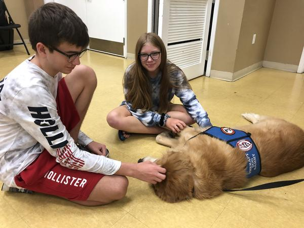 Siblings William and Elizabeth Olson pet therapy dog Sammy. William, 15, is a sophomore at Douglas and was shot at school on Feb. 14. Dogs like Sammy have helped him feel calm and safe in school since.