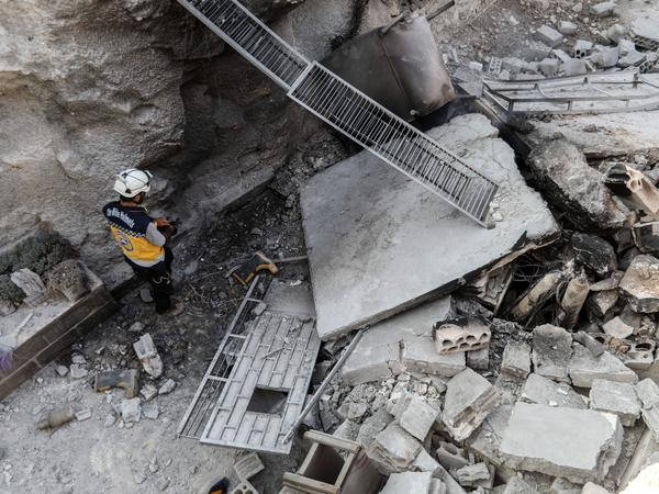 "A member of the Syrian Civil Defense, also known as the ""White Helmets,"" walking through the wreckage of their center, which was destroyed Thursday by government forces in the town of al-Tamana in rebel-held Idlib province."