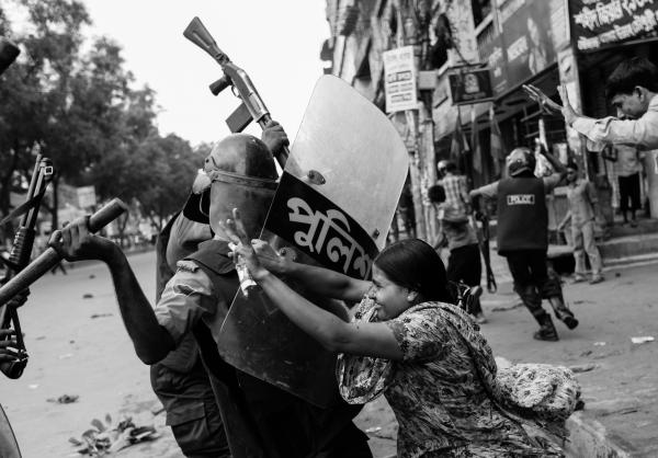 Rahela Akhter, a Bangladeshi garment worker, tries to resist beating from a police officer in riot gear during a protest in Dhaka, June 2010. Dozens of garment workers were injured in clashes with police when they took to the streets demanding higher wages.