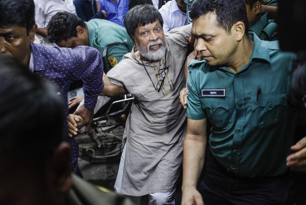 Shahidul Alam, surrounded by police, arrives at a Dhaka court on Aug. 6. Nobel laureates and human rights groups have called for his release.