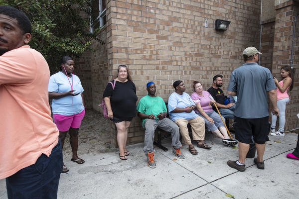 Evacuees sit outside the temporary shelter at Trask Middle School before Hurricane Florence arrives in Wilmington, N.C., on Thursday.