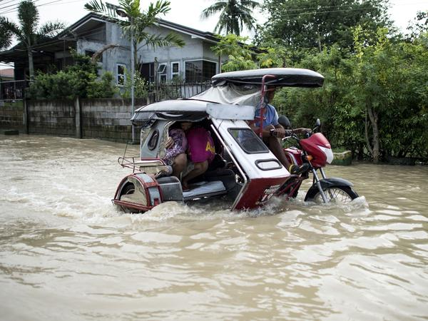 A rickshaw driver wades through a flooded street in Calumpit, Bulacan in the Philippines on Monday.