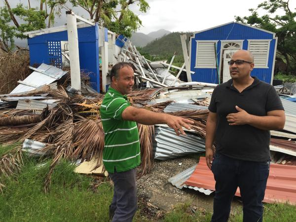 Jan Carlo Perez (right) talks with a neighbor this month in front of a house demolished in Patillas, Puerto Rico, by Hurricane Maria in September.