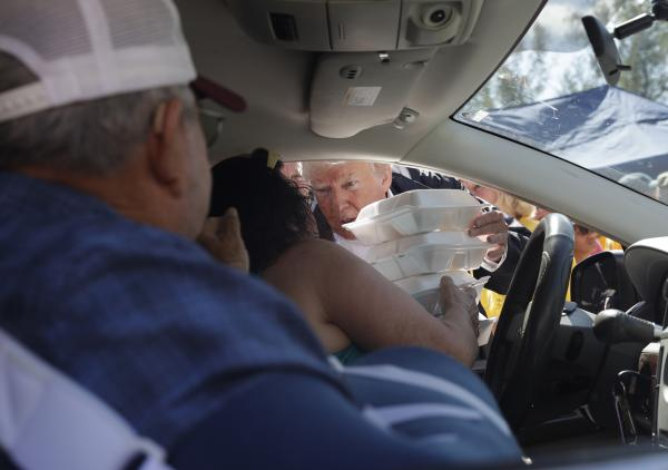 President Trump hands out food on Wednesday at Temple Baptist Church in New Bern, N.C., where food and other supplies are being distributed.