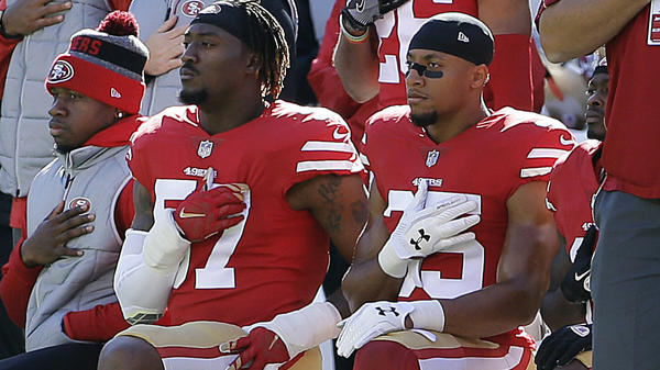 Safety Eric Reid, seen here at right kneeling before a San Francisco 49ers game last November, has signed a new contract with the Carolina Panthers, ending his free agency.
