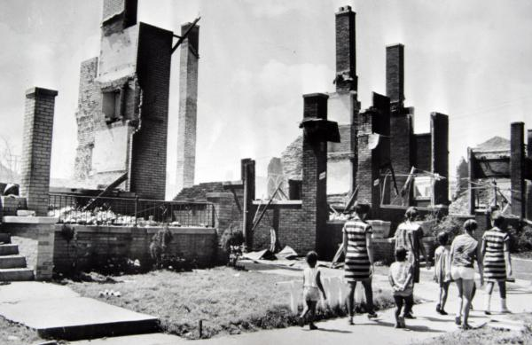 Women and children stroll past the burned remains of homes a short distance from 12th Street, which was a center of the riot activity.