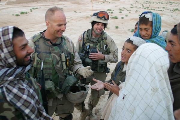 Kit Parker (second from left) and Aaron Chapman (third from left) meet with village elders in the village of Loy Kariz, Afghanistan in 2003.