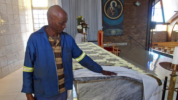 Regina Mundi caretaker Danny Dube uncovers a corner of the church's main altar. Dube says a South African police officer smashed off the end of the marble structure with a rifle butt during the Soweto Riots in the 1970s and '80s.