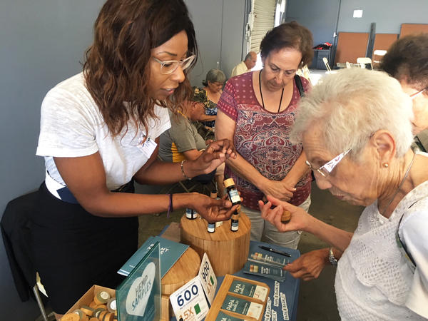 Megan Baker (left) of Papa & Barkley Co., a Cannabis company based in Eureka, Calif., shows Shirley Avedon of Laguna Woods different products intended to help with pain relief.