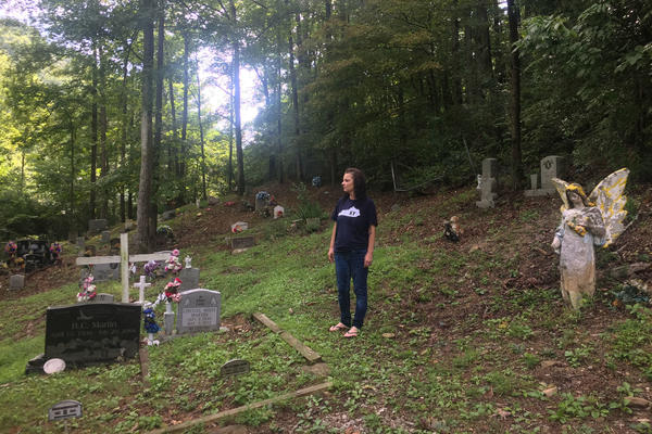 BarbiAnn Maynard walks between the headstones at her family's cemetery, pointing out her grandparents and her cousins. Her deep roots in Martin County are one reason she says she'll never leave, despite the lack of a reliable supply of clean drinking water.