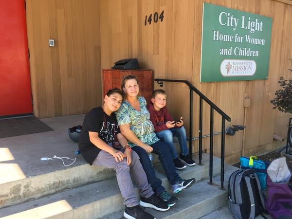 Caydden, 14, and Keston, 11, sit outside a homeless shelter in Boise. They've been searching for housing for three months.