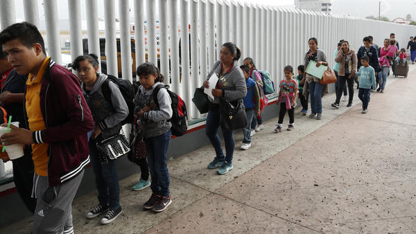 """People line up to cross into the United States to begin the process of applying for asylum near the San Ysidro port of entry in Tijuana, Mexico. Homeland Security's watchdog says immigration officials were not prepared to manage the consequences of its """"zero tolerance"""" policy at the border."""