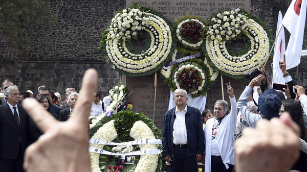 Mexican President-elect Andres Manuel Lopez Obrador, center, stands Tuesday with Ana Ignacia Rodríguez Marquez, a former leader of the student movement of 1968, at a ceremony marking the 50th anniversary of the 1968 Tlatelolco massacre, at the Tres Culturas square in Mexico City.