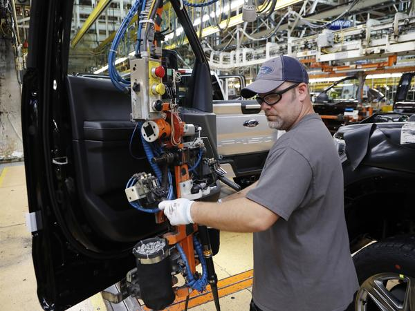 A worker installs a door on a 2018 Ford F-150 truck at an assembly plant in Dearborn, Mich., on Sept. 27.