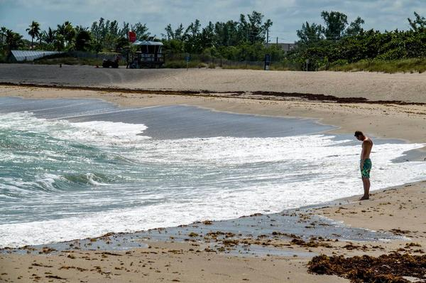 Zach McGowen, of Jupiter, checks out the water for possible surfing conditions south of Jupiter inlet on Monday. Several county-managed beaches in Palm Beach County reopened on Friday.