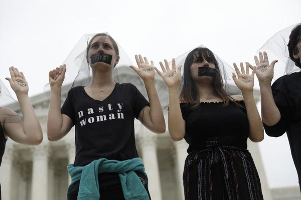 Women stand in silent protest outside the U.S. Supreme Court building.