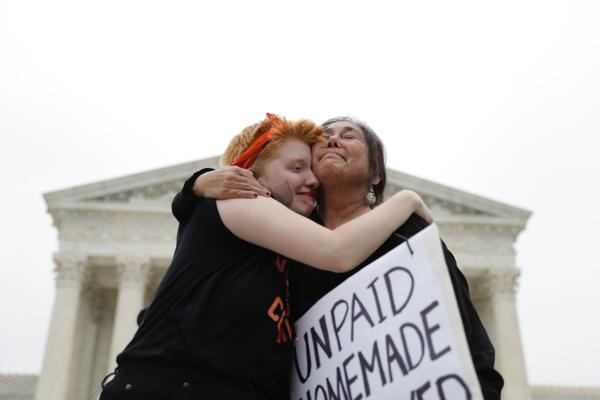 Activists hug outside the Supreme Court during a protest.