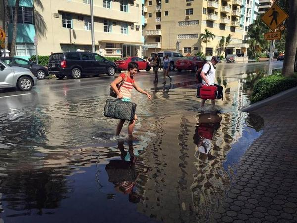 Oakley and Casey Jones, tourists from Idaho Falls, navigate the flooded streets of Miami Beach as they try to make their way to their hotel on Collins Avenue and 30th Street during a King Tide on Monday, Sept. 28, 2015.