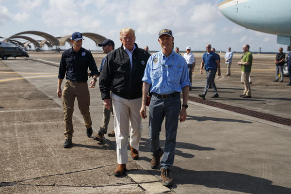 Florida Gov. Rick Scott (right) and President Trump walk over to speak with reporters after arriving on Monday at Eglin Air Force Base in Florida to visit areas affected by Hurricane Michael.
