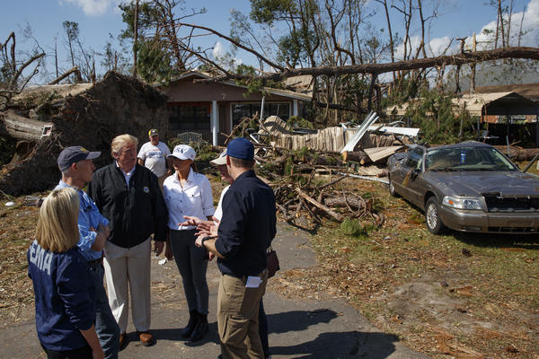 President Donald Trump talks with Homeland Security Secretary Kirstjen Nielsen (from left), Florida Gov. Rick Scott, Trump, first lady Melania Trump, Lynn Haven Mayor Margo Anderson, and FEMA director Brock Long, as they tour a neighborhood on Monday affected by Hurricane Michael.