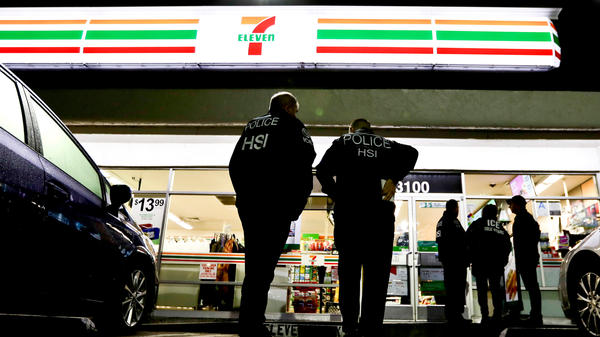 U.S. Immigration and Customs Enforcement agents serve an employment audit notice at a 7-Eleven convenience store in Los Angeles. California is divided over the state's new sanctuary law, which took effect earlier this year.