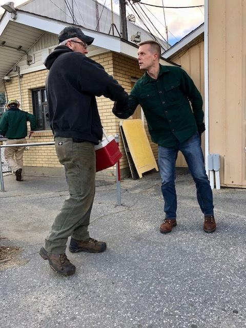 Democrat Jared Golden shakes hands with a worker outside the Verson Paper Mill in Jay, Maine.